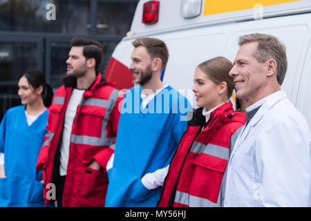 ambulance doctors working team smiling and standing in front of car - Stock Photo