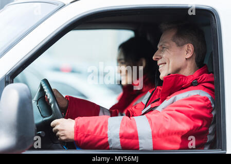 smiling male and female paramedics sitting in ambulance - Stock Photo