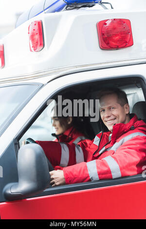 happy male and female paramedics sitting in ambulance - Stock Photo