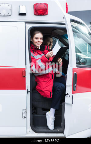 smiling paramedic sitting in ambulance and holding clipboard - Stock Photo