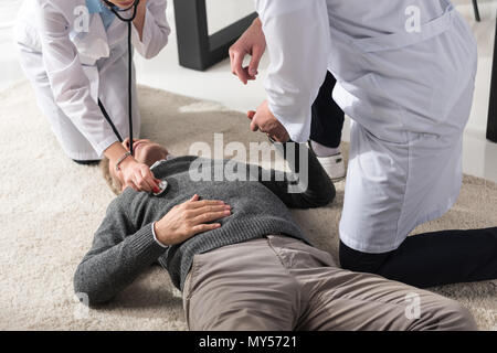 cropped image of doctor checking unconscious middle aged man palpitation with stethoscope - Stock Photo