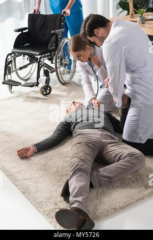 female doctor checking unconscious man palpitation with stethoscope - Stock Photo