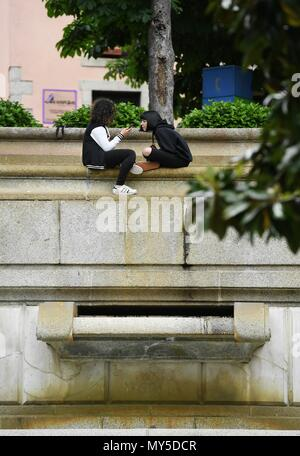 Madrid, Spain. 5th June, 2018. Two girls sit by a garden at El Escorial, Spain, on June 5, 2018. Credit: Guo Qiuda/Xinhua/Alamy Live News - Stock Photo