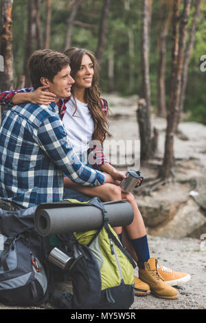 young couple with backpacks relaxing in forest while having hiking trip - Stock Photo