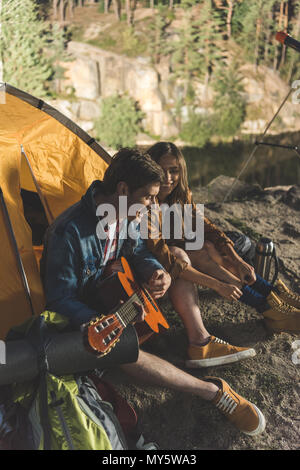 happy young man playing guitar for girlfriend in hiking trip - Stock Photo