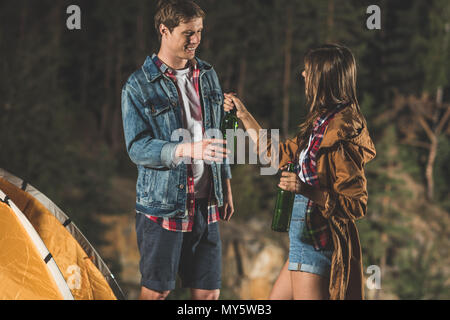 young couple sharing beer in hiking trip at night - Stock Photo