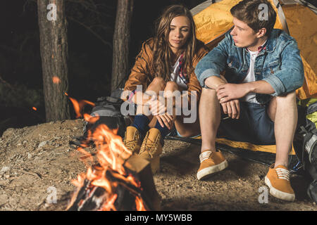 young happy hikers sitting next to campfire - Stock Photo
