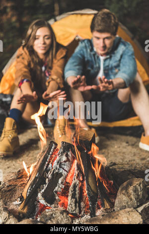 couple warming hands with bonfire on hiking trip - Stock Photo