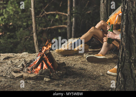 couple on hiking trip drinking beer while sitting next to campfire - Stock Photo
