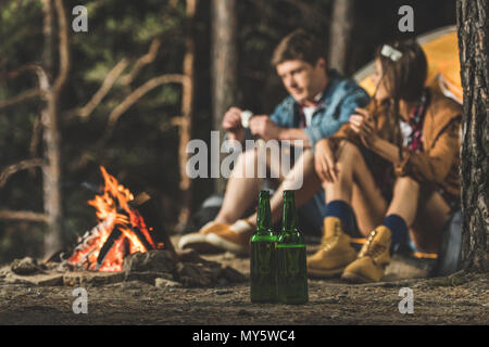 couple sitting next to hiking tent with two bottles of beer on foreground - Stock Photo