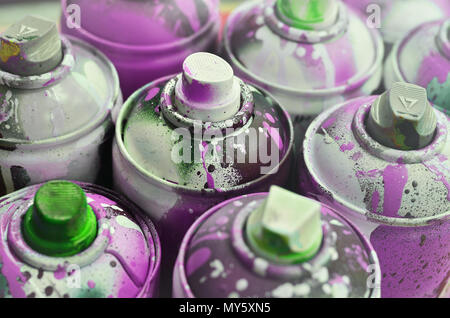 A lot of used spray cans of paint close-up. Dirty and smeared cans for drawing graffiti. The concept of a sweeping and careless drawing of paint. Crea - Stock Photo