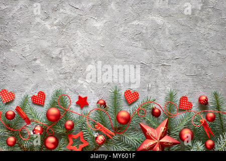 Green and red Cristmas background with fir twigs, hearts and Christmas trinkets on concrete stone background, text space - Stock Photo