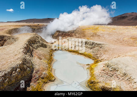 The volcanic activity of Sol de Mañana in Bolivia between Chile and the Uyuni Salt Flat. Mud pits and fumaroles with water vapor trails in the Andes. - Stock Photo