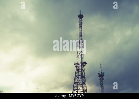 Radio telecommunications tower, Mobile phone tower and old steel pipe in storm clouds. dramatic landscape with cloud storm cloud and metal TV tower - Stock Photo