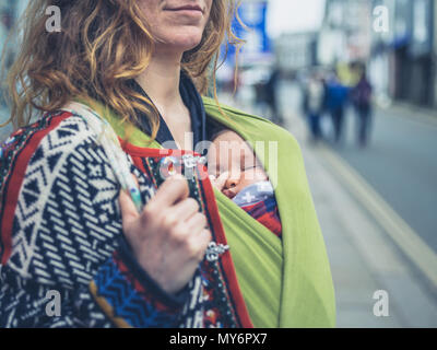 A young mother in the street with her baby in a carrier sling - Stock Photo