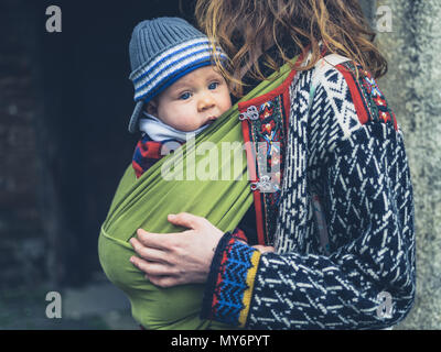 A young mother with her baby in a carrier sling is standing outside a historic building - Stock Photo