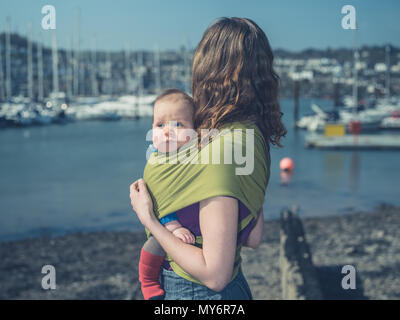 A young mother is standing in a harbor on a sunny day with her baby in a sling - Stock Photo