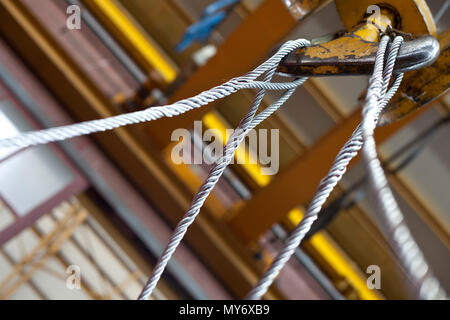closup on yellow industrial hook with steel cables - Stock Photo