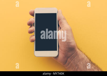 Smartphone with blank screen in male hand, retro toned image - Stock Photo