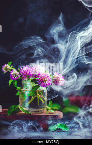 Clover flowers in a glass jar with rising smoke. Magic summer concept on a dark background with copy space - Stock Photo