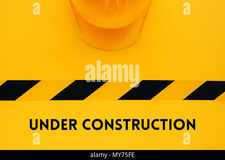 Under construction concept with yellow protective helmet, top view flat lay minimalistic composition - Stock Photo