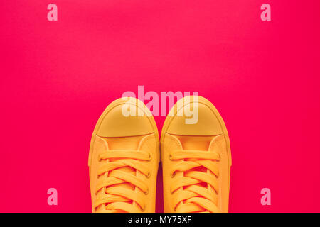 Yellow canvas shoes sneakers on neon pink background, top view with copy space - Stock Photo