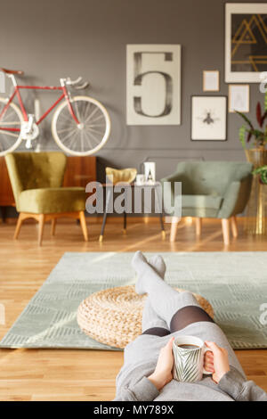Young lady lying on a green carpet with a cup of tea in her hands and her legs on a pouf in a vintage living room interior with blurred background - Stock Photo