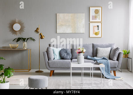 Real photo of a grey sofa with cushions and blanket standing in elegant living room interior behind a white table and next to a gold lamp and grey wal - Stock Photo