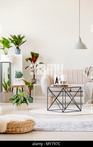 Real photo of a beige living room interior with a sofa standing behind a black table, under a lamp and next to plants - Stock Photo