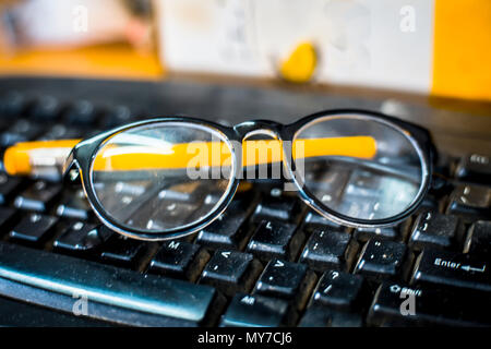 Close up of reading glass and a ball pen with a mouse on keyboard. - Stock Photo