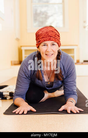 Portrait of senior woman practicing pigeon yoga pose (kapotasana) in yoga studio - Stock Photo