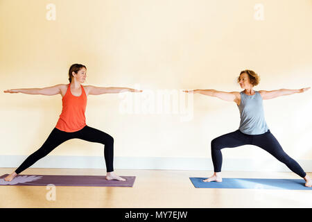 Two women practicing  warrior two (virabhadrasana II) yoga pose in yoga studio - Stock Photo