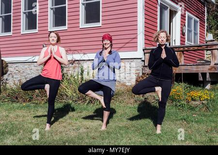 Three women practicing yoga tree pose (vriksasana) in garden - Stock Photo