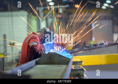 Welder using grinder in trailer factory - Stock Photo