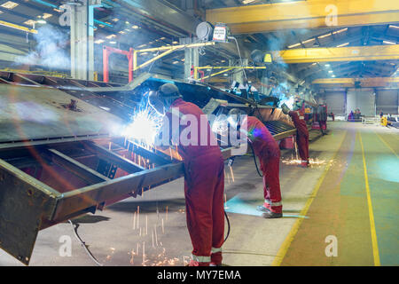 Line of welders working on chassis construction in trailer factory - Stock Photo