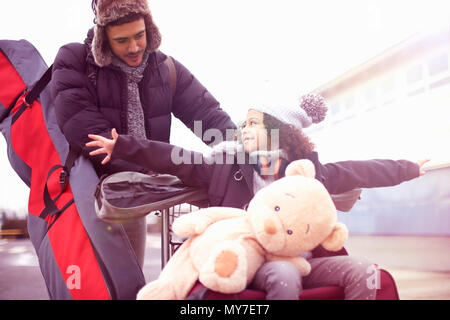 Father pushing girl on luggage trolley - Stock Photo