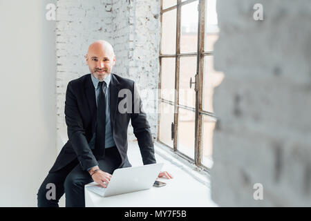 Portrait of businessman sitting on windowsill using laptop - Stock Photo