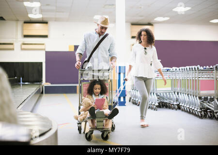 Family with girl on luggage trolley in airport - Stock Photo