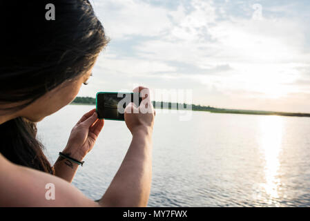 Young female tourist photographing sunset on Chobe River, Botswana, Africa - Stock Photo