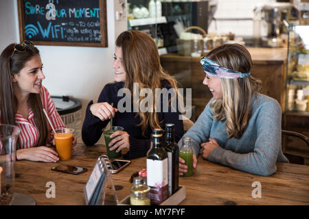 Three young female friends with vegetable juice chatting in cafe - Stock Photo