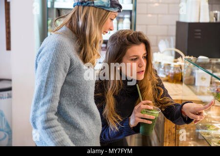 Young woman and friend looking at fresh food display cabinet in cafe - Stock Photo