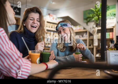 Three female friends, sitting in cafe, drinking smoothies, laughing - Stock Photo