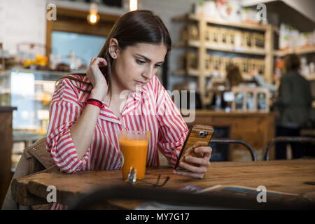 Young woman sitting in cafe, using smartphone, smoothie on table in front of her - Stock Photo