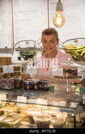 Portrait of sales assistant in cafe, standing behind counter, smiling - Stock Photo