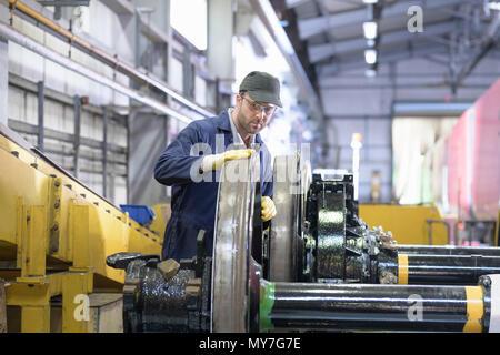 Engineer inspecting locomotive wheels for wear in train engineering factory - Stock Photo