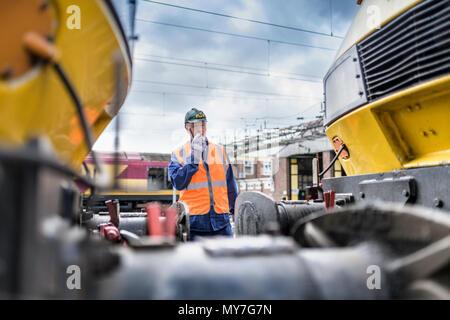 Engineer using walkie-talkie to guide locomotive - Stock Photo
