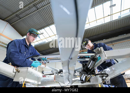 Apprentice engineers working on locomotive pantograph in train engineering factory - Stock Photo