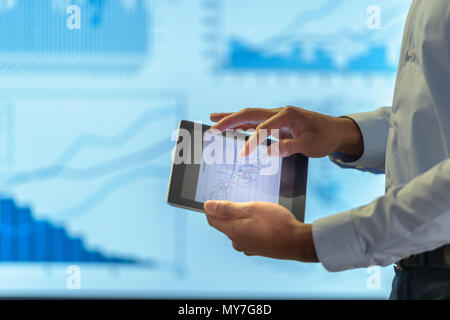 Man using business digital tablet during presentation with graphs and charts, close up