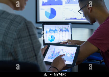 Businessman and woman using screens with graphs and charts in business meeting, close up - Stock Photo