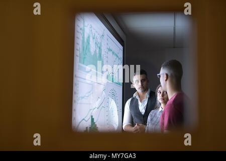 Business team in meeting seen through glass door - Stock Photo
